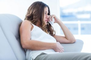 Upset young woman on couch: All About Women Pregnancy & Prenatal Care Blog