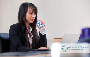 woman drinking water at her desk